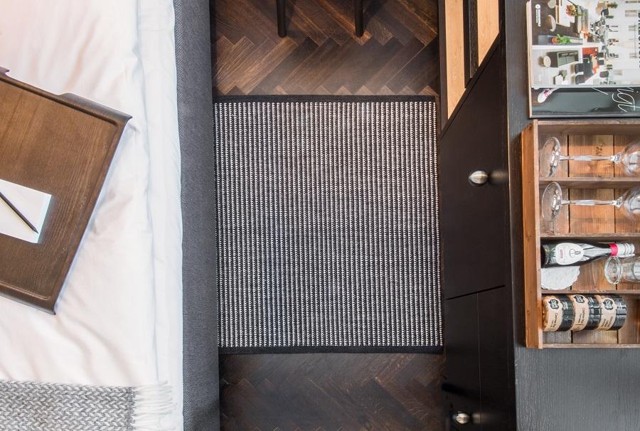 Handvävd matta under säng på Miss Clara hotel.