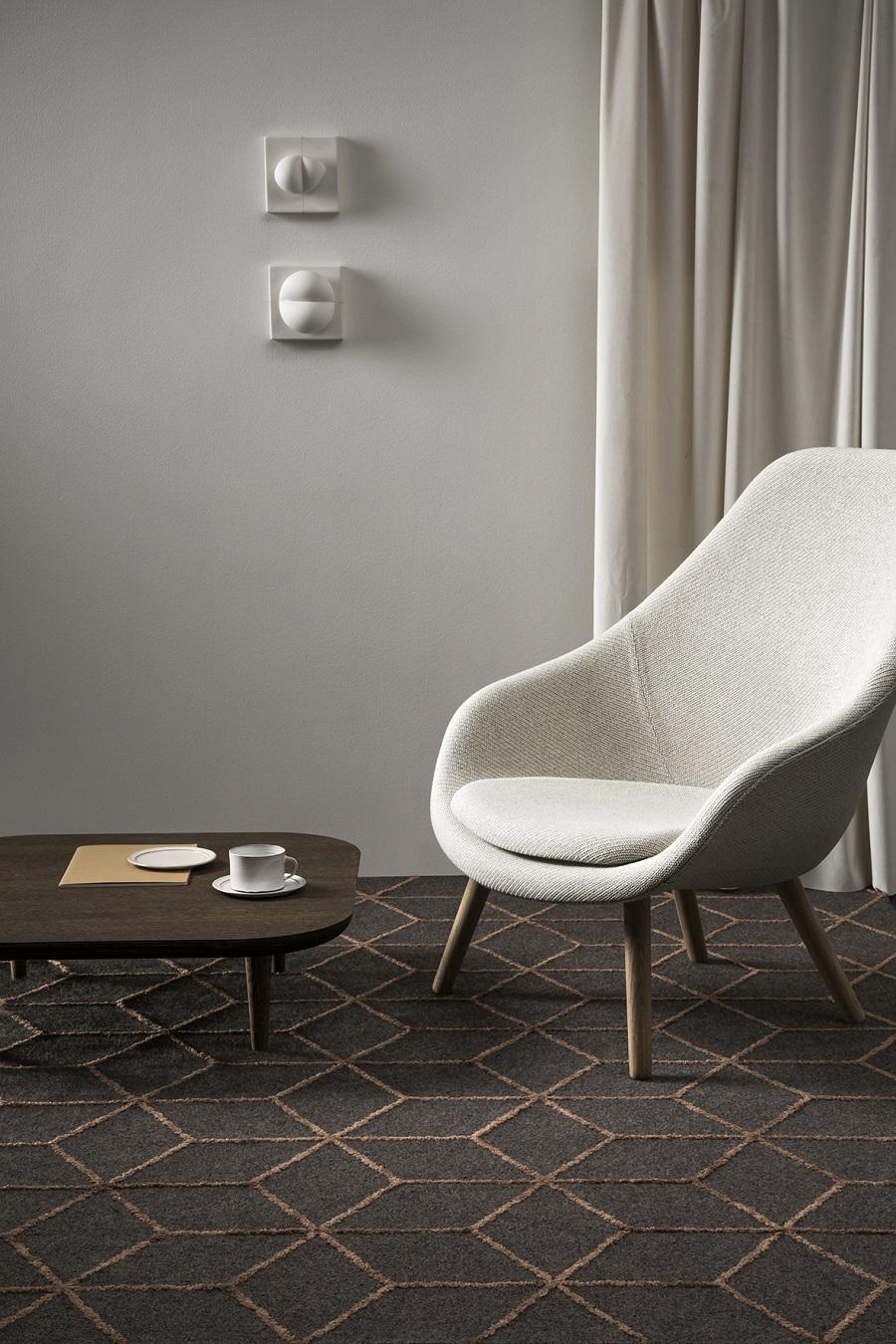Handtuftad matta Vega Aster Design under fåtölj, från Ogeborg Design Collection.