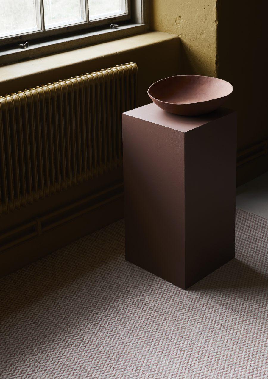 Handvävd matta Pixie från Ogeborg Design Collection under piedestal med skål på..