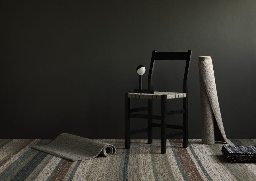 Handvävd matta Nova Stripe från Ogeborg Design Collection under svart stol.